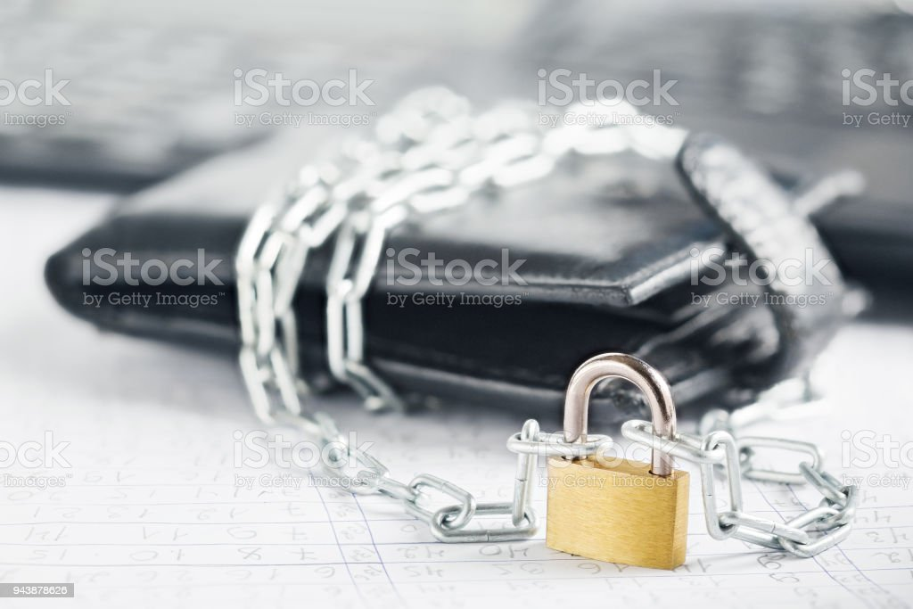 Leather wallet with lock and chain on background  computer. Ð¡oncept of protecting electronic money and safety personal finances. Security of financial transactions in cashless and cash settlements. stock photo
