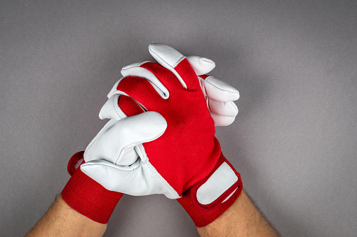 Leather work gloves for a man's hands. Gray background.