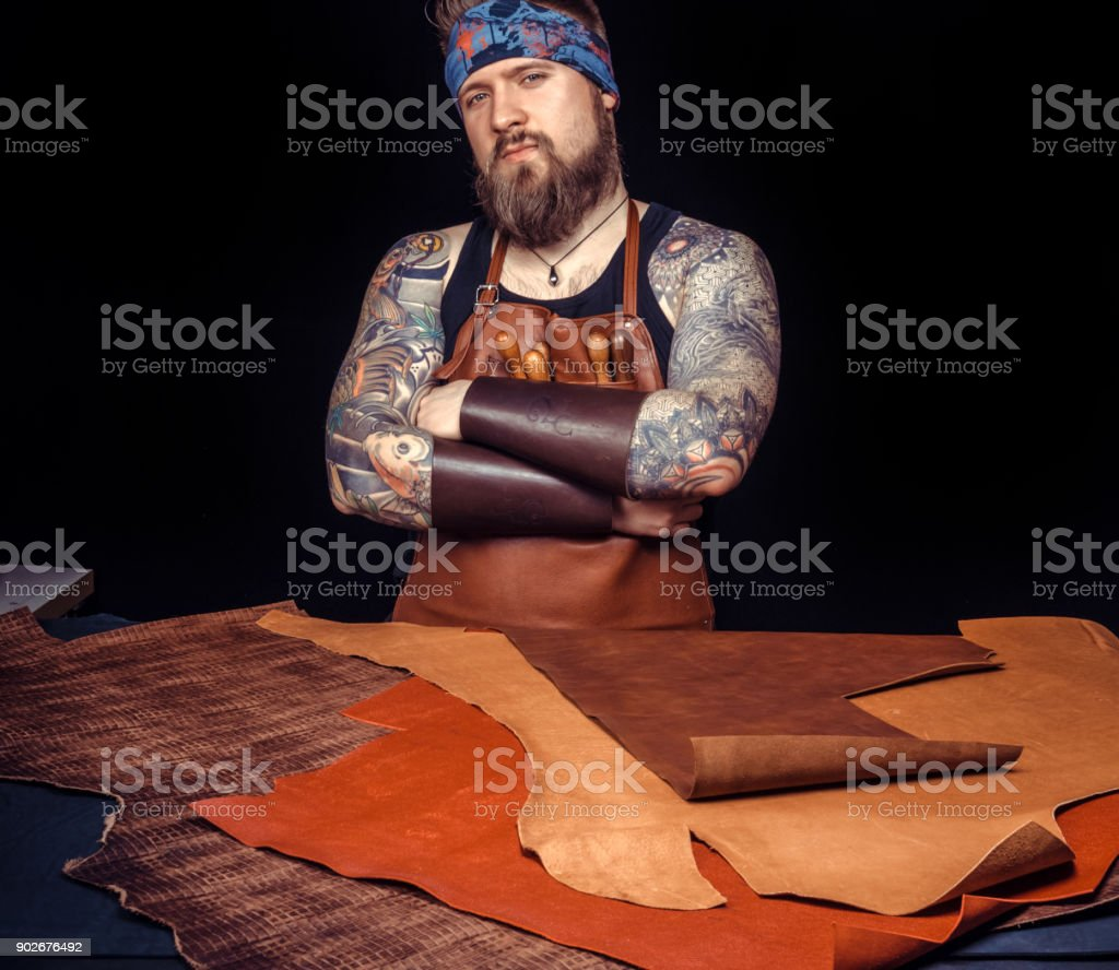 Leather workman works with leather goods stock photo