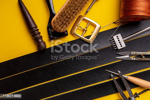 istock Leather workplace. Hand craft or leather working. Materials, accessories and working tools on leather craftman's work desk 1135214663