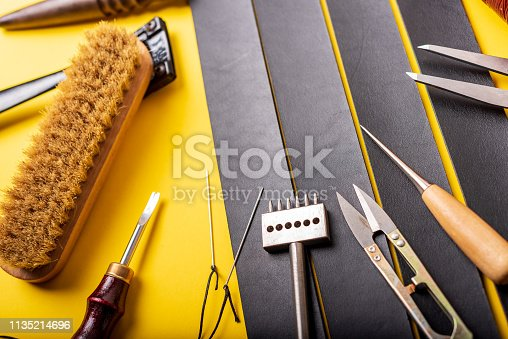 istock Leather workplace. Hand craft or leather working. Materials, accessories and working tools on leather craftman's work desk 1135214696