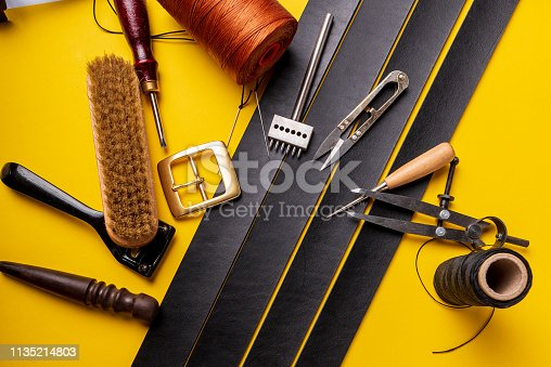 istock Leather workplace. Hand craft or leather working. Materials, accessories and working tools on leather craftman's work desk 1135214803