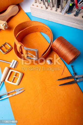 istock Leather workplace. Hand craft or leather working. Materials, accessories and working tools on leather craftman's work desk 1135214859