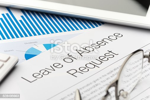 Leave of absence request form on a desk with paperwork and digital tablet. Close up.