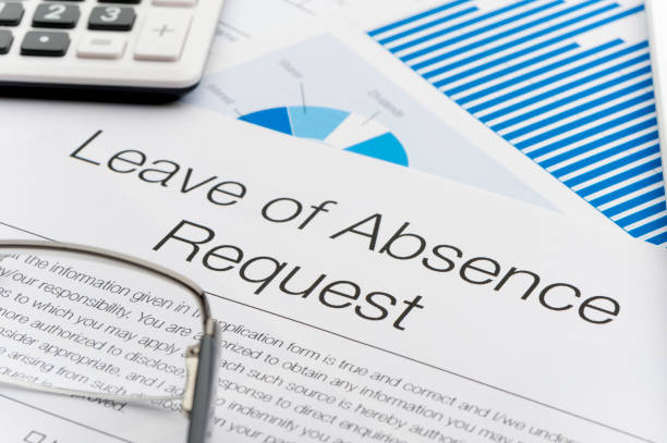 Leave of absence request form on a desk with paperwork. stock photo