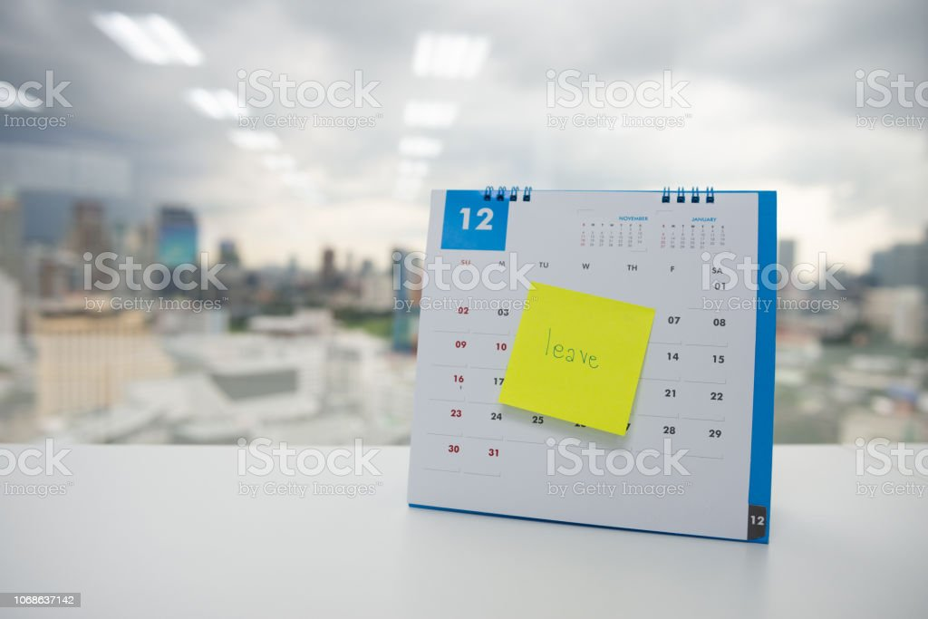 Leave on paper note stick on the calendar of December for year end holidays concept stock photo