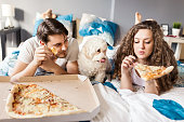 Leave something for me. Couple and thier dog enjoying pizza in bed.