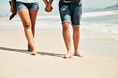 Cropped shot of an affectionate young couple going for a relaxing walk along the beach