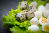 Leaves of a green salad with quail eggs in a skolrupa and without, by, on a dark wooden table.
