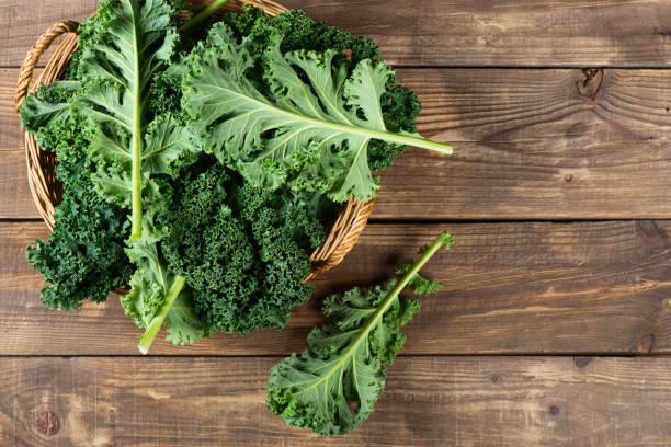 Leaves of  raw kale, above view. Top view of freshly harvested kale in a wicker basket on a rustic wooden background with copy space. kale stock pictures, royalty-free photos & images