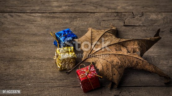istock Leaves on wooden table and colorful gift packages 914023376