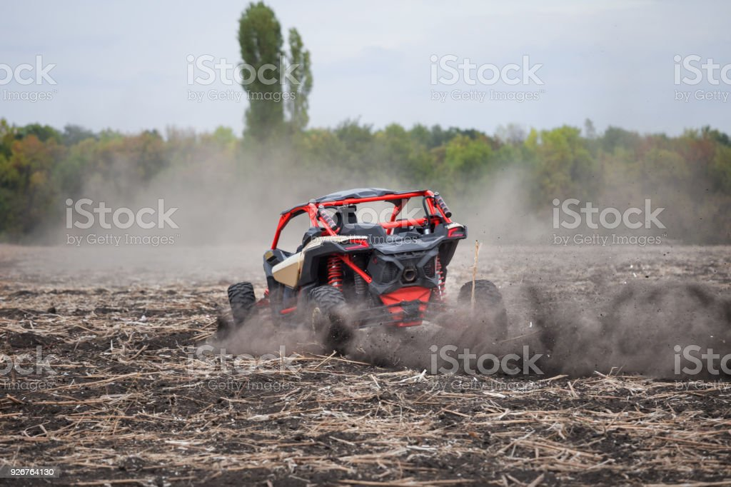 Leaving a quad bike with driver in plowed field stock photo