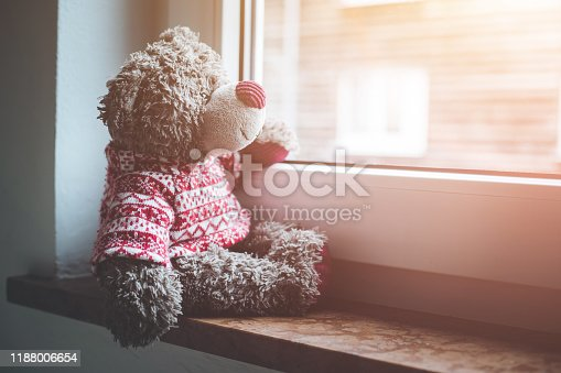Cute teddy bear is sitting on the windowsill, looking out of the window
