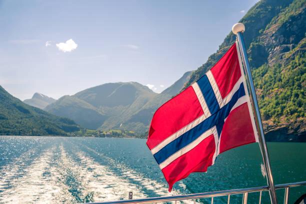 het verlaten van flam port in noorwegen. noorse vlag vliegen op het achterdek van de fjord cruiseschip - noorse vlag stockfoto's en -beelden