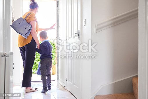 A mother and son on their way out of the front door for his first day at school