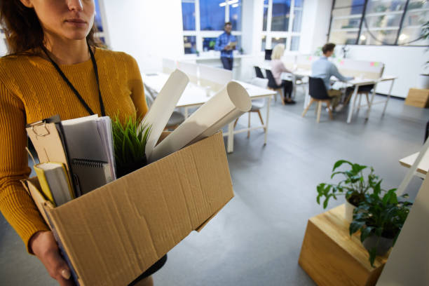 Leaving office after dismissal Serious sad woman in sweater carrying cardboard box full of stuff and leaving office after dismissal quitting a job stock pictures, royalty-free photos & images