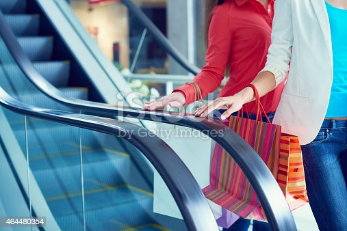 Women with shopping bags moving down on escalator in shopping mall