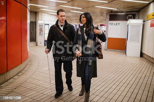 Visually impaired man walking with his friend leaving a subway station, he is using a white walking cane for guidance as well as holding his friends arm.