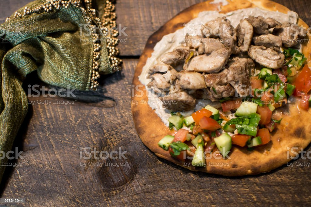 Lebanese chicken shish taouk on pita elevated view on rustic wood background stock photo