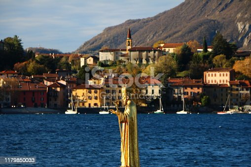 Lecco, Italy. Lake view with a statue of San Nicolo, a saint patron of Lecco.