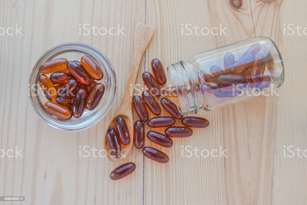 Lecithin gel vitamin supplement capsules in a cup, a spoon and a bottle on wooden table. stock photo