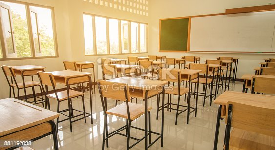 istock Lecture room or School empty classroom with desks and chair iron wood for studying lessons in high school thailand, interior of secondary education, with whiteboard, vintage tone educational concept 881192038