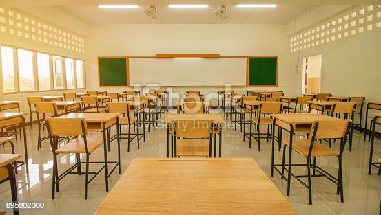 1047047834 istock photo Lecture room or School empty classroom with desks and chair iron wood for studying lessons in high school thailand, interior of secondary education, with whiteboard, vintage tone educational concept 895802000
