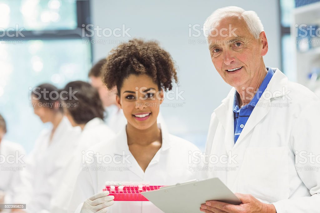 Lecturer and student smiling at camera in the lab stock photo