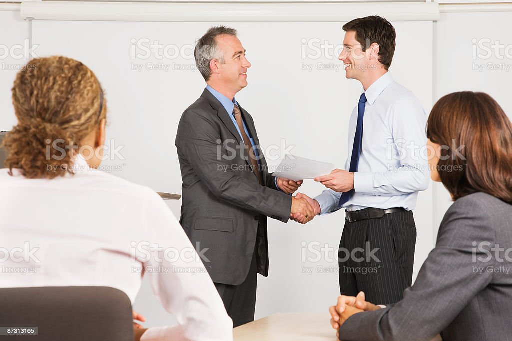 A lecturer handing a certificate to a student stock photo