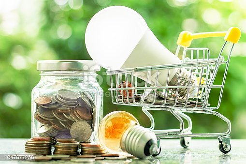 Led lamp in mini shopping cart or trolley  with glowing light bulb and money coins in the glass jar against blurred natural green background for finance, saving energy and environment concept