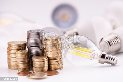 istock Led lamps and piggy bank stand on money coins on a white background 1086592054