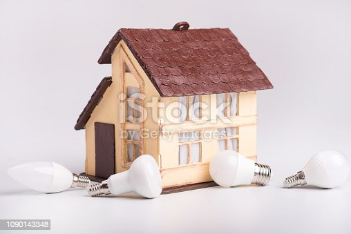 istock Led lamps lie near the house layout on a white background. Theme energy saving in the house 1090143348