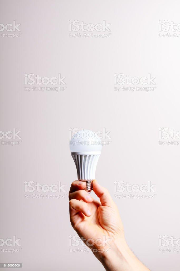 Led light bulb in male hand. stock photo