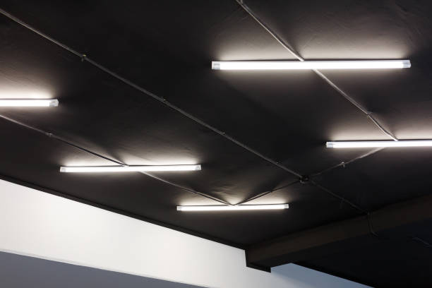 led tube lights on black office ceiling. minimal loft design - światło led zdjęcia i obrazy z banku zdjęć