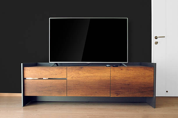 led tv on tv stand with black wall - flat screen stock photos and pictures