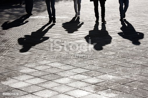 Legs and shadow of five young person approaching on city street pedestrian sidewalk