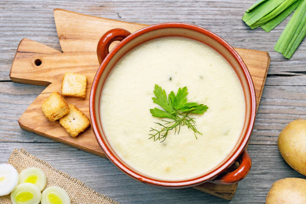leek and potato soup top view leek and potato soup and ingredients on wooden cutting board leek stock pictures, royalty-free photos & images