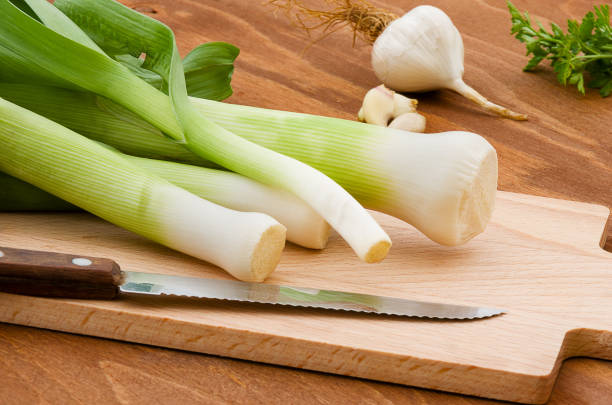 Leeks cut into slices on wooden plank on wooden background. - foto stock