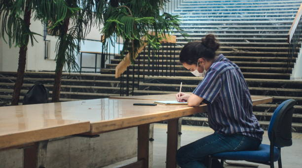 Left angle isolated young college student taking notes alone in the library stock photo
