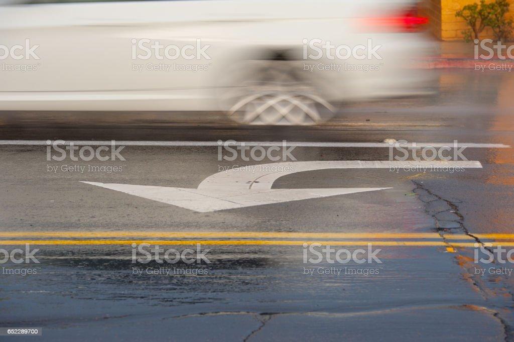 Left arrow painted on rain wet California street stock photo