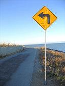 A left curve sign along a nature trail.