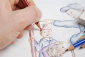 A hand is drawing and painting a picture and there are some colored pencils and a eraser.