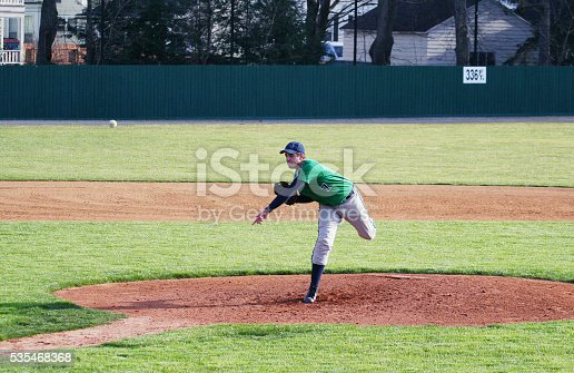 This teenage high school student baseball team player - a left-handed pitcher - has just thrown a baseball pitch from the baseball diamond pitcher's mound. He lands on his right leg to finish his delivery while the ball flies towards home plate.