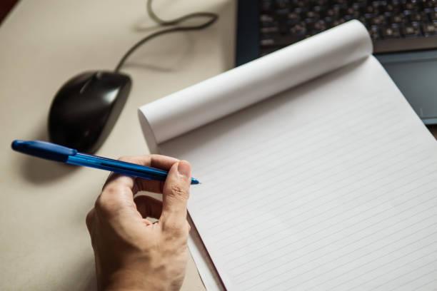 homme gauche écrivant sur le papier de rapport - gaucher photos et images de collection