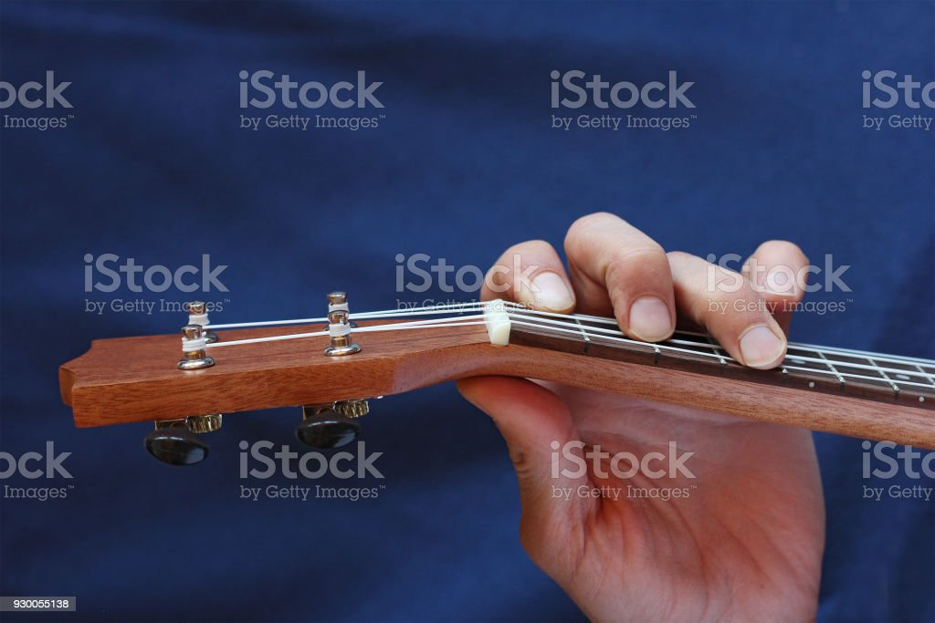 Left Musician Hand Clamps The Chord On The Ukulele Top View Stock
