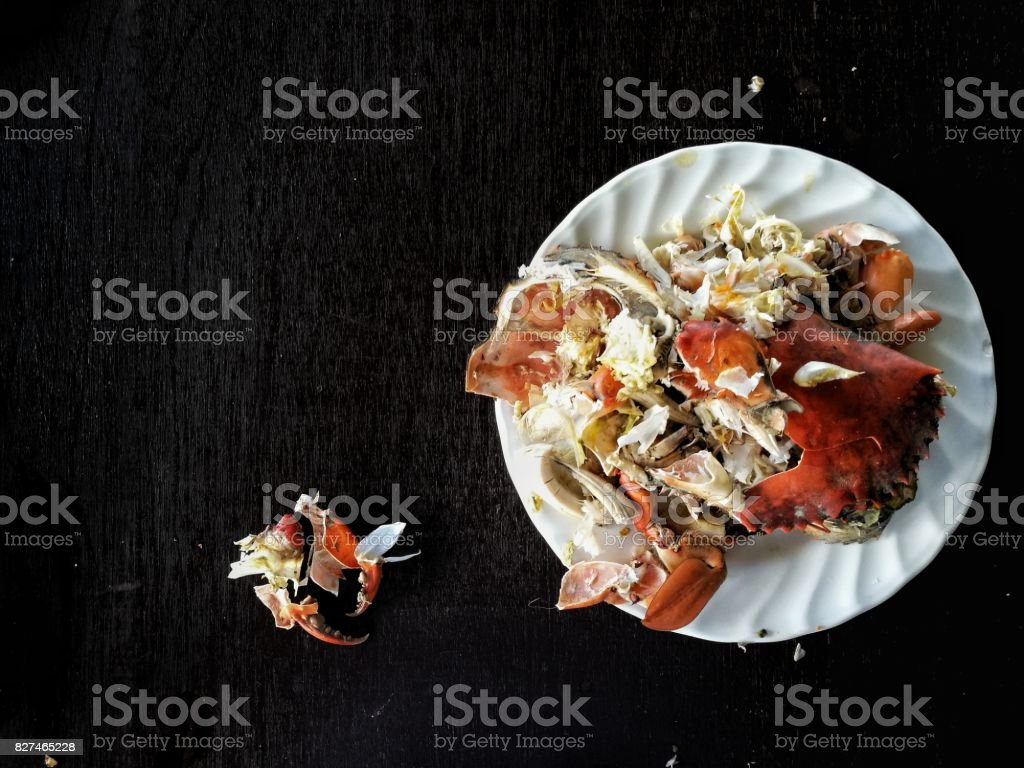 left over food trash, crab shell on a plate from a streamed crab on dark wood table. stock photo