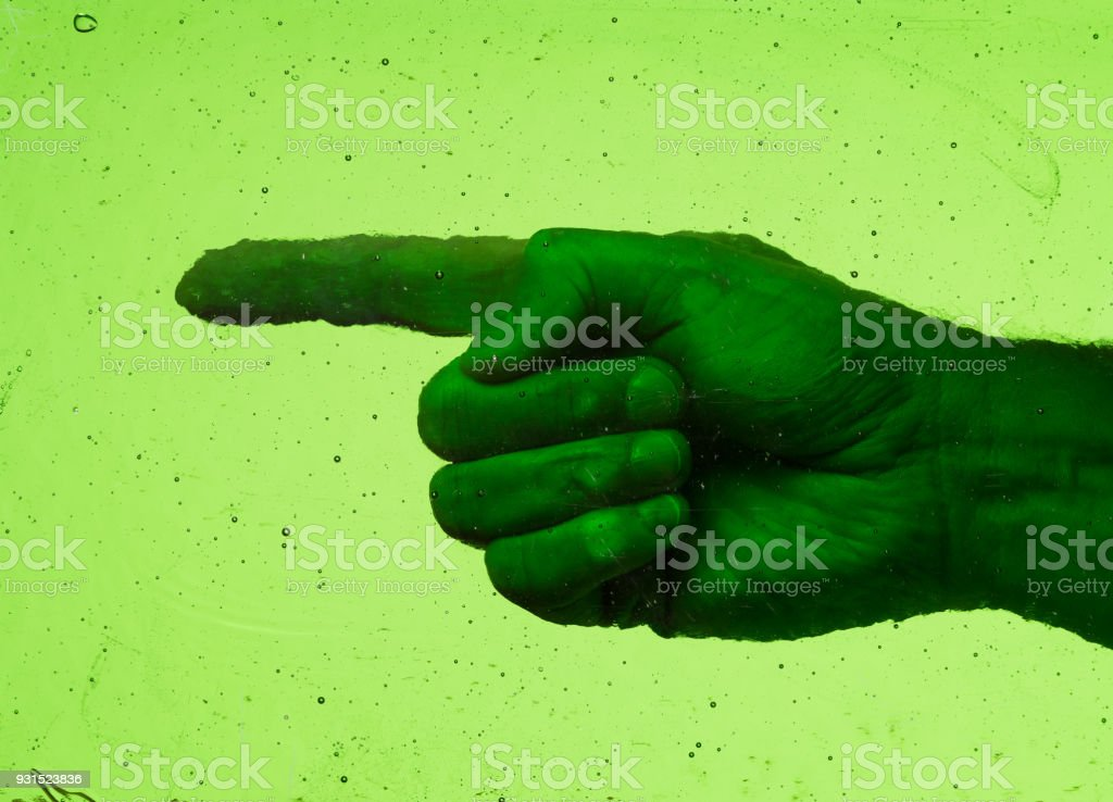 Left pointed finger behind a pane of weathered vintage green glass with bubbles and scratches stock photo