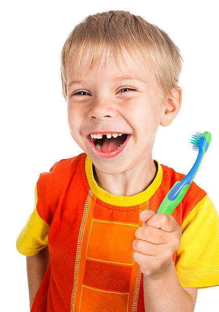 left-handed smiley boy with toothbrush stock photo