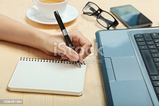 The left-hander writes in a notebook on a wooden background