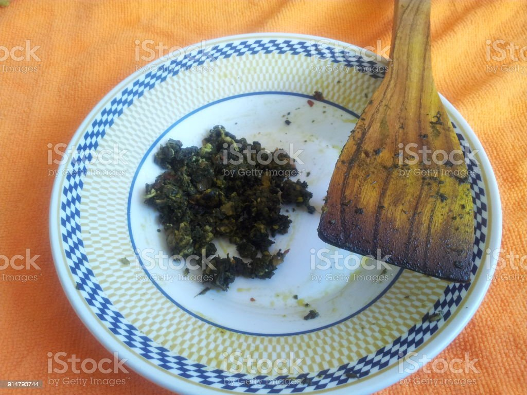leftover of Palak Saag in a ceramic plate with wooden spoon stock photo